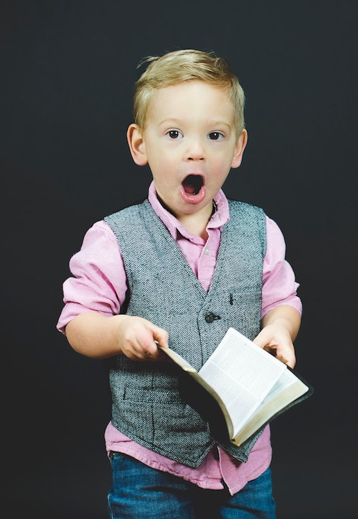 Boy with book looking surprised